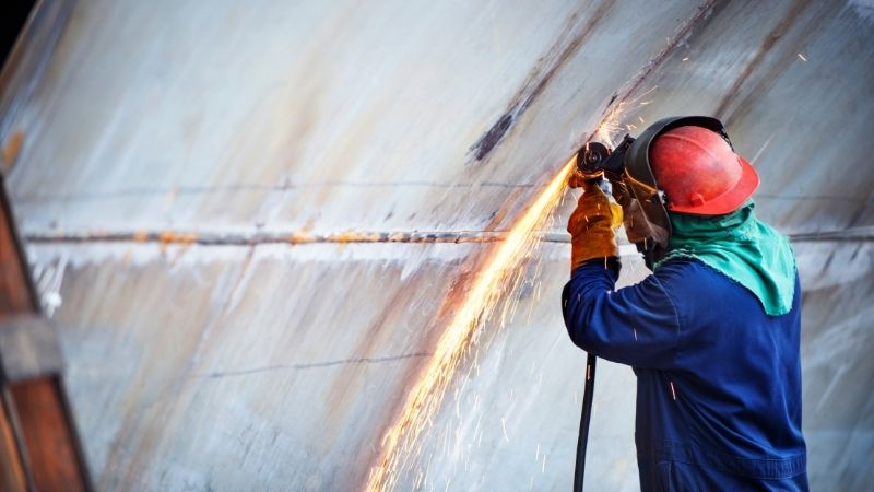 person using grinder in shipyard