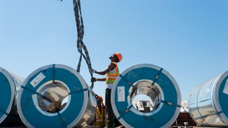 workers handling steel coil cargo