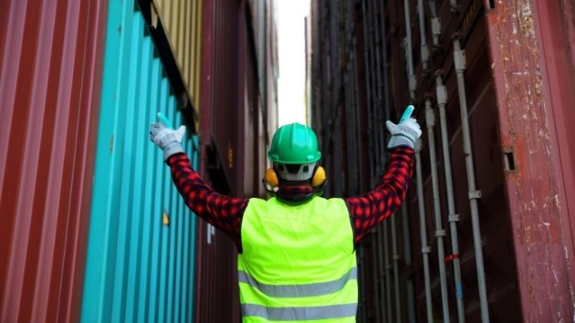 person in ppe with arms raised at cargo containers