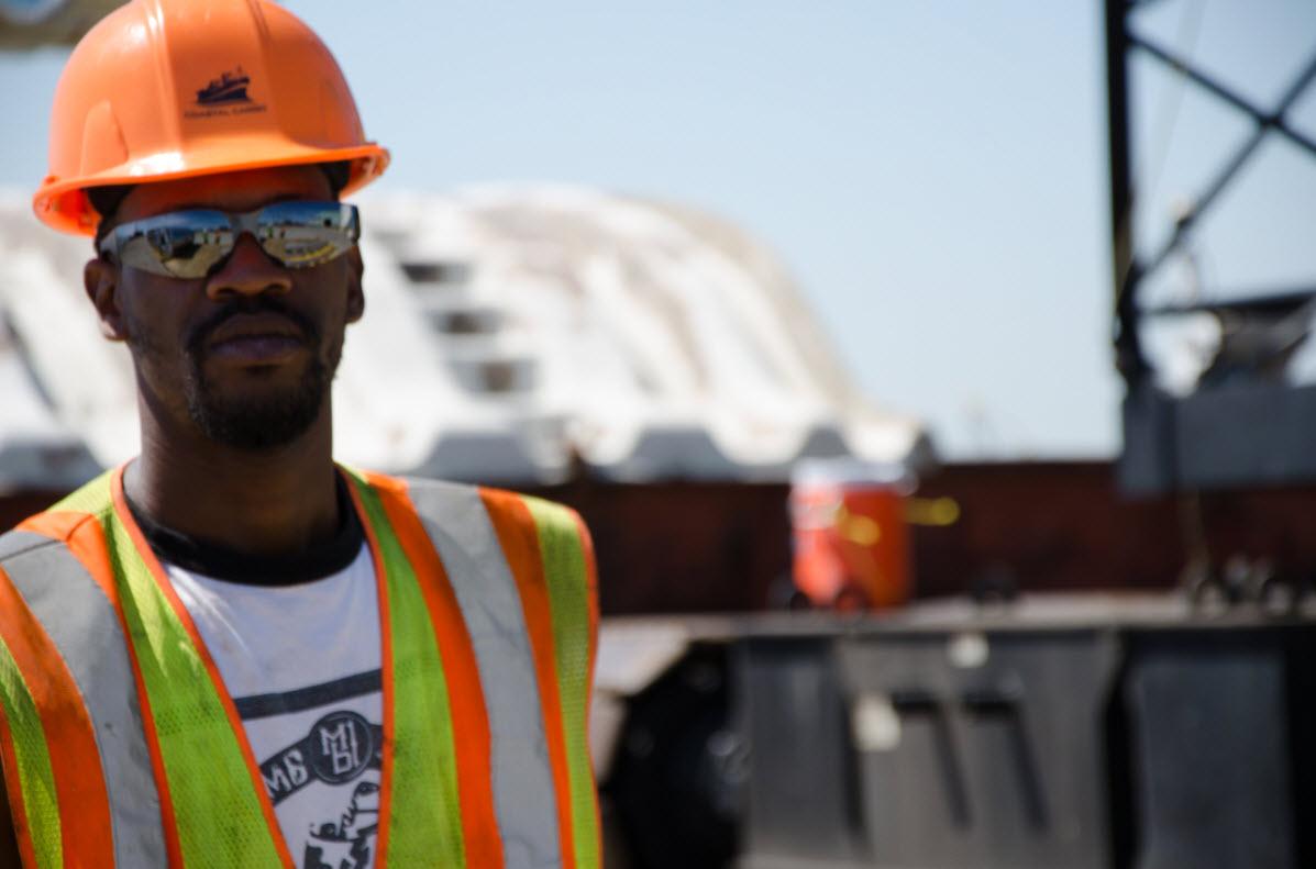 Shipyard worker wearing hard hat and safety vest
