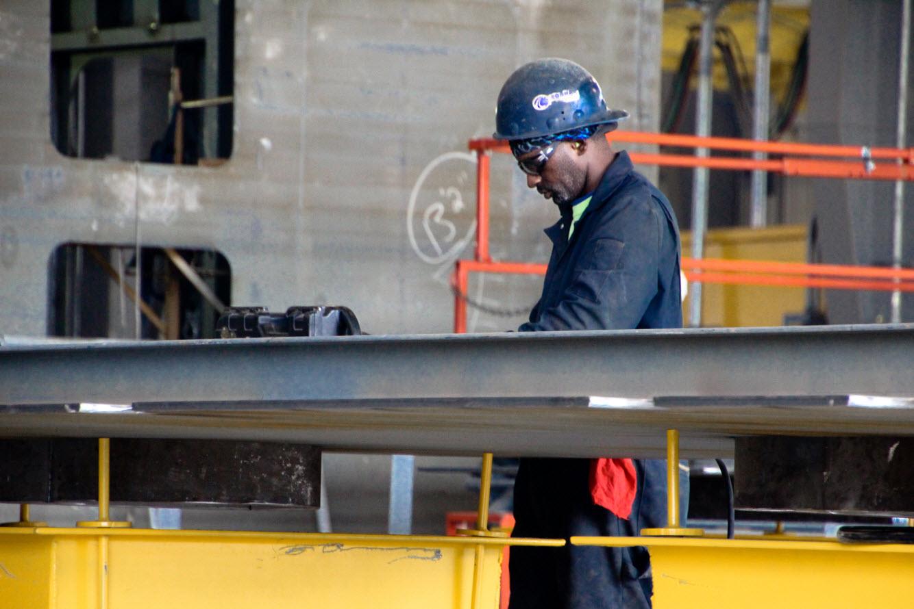 Worker measuring metal