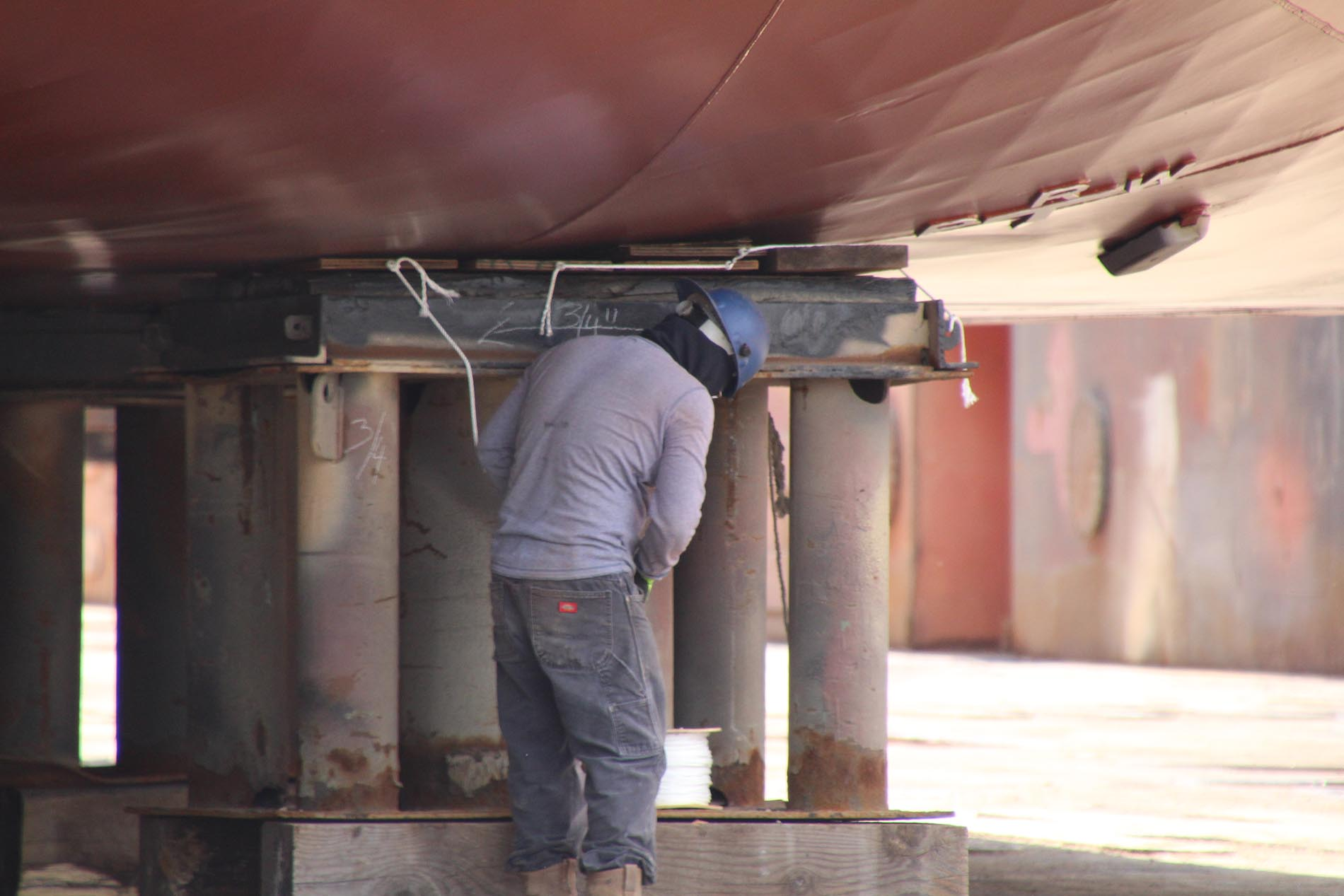 Painter under ship in dry dock