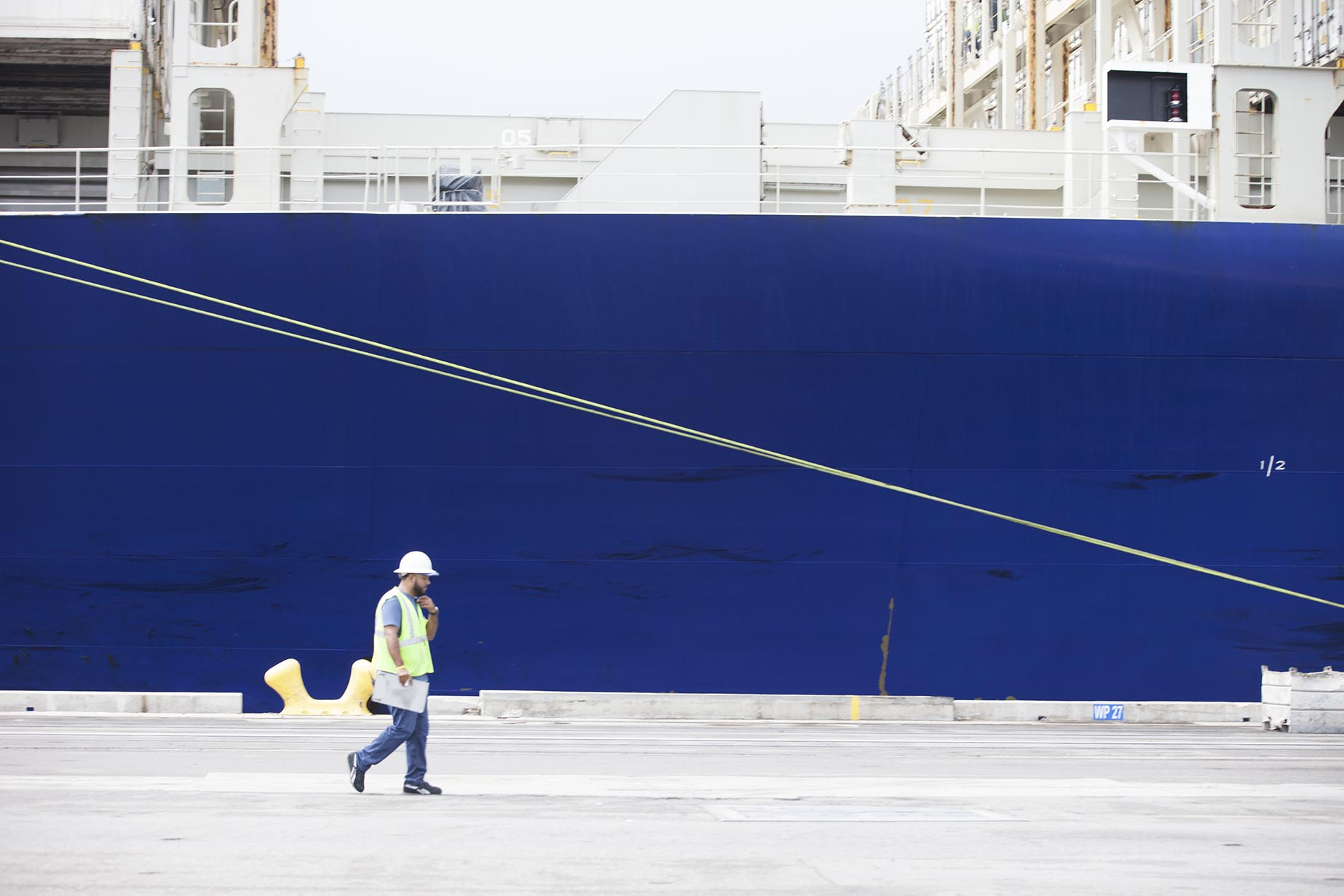 Man walking near blue ship