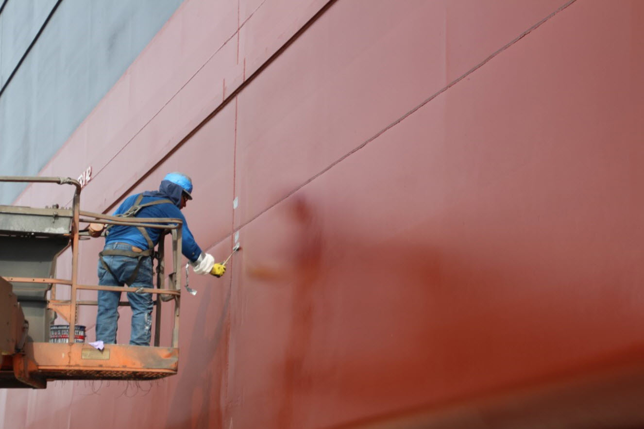 Worker painting ship