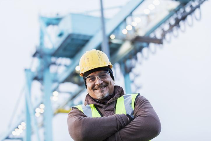 worker standing in front of crane