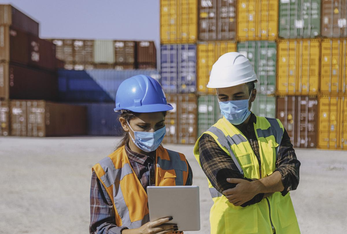 Two workers wearing masks in a container yard