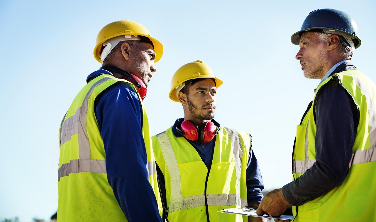 three male workers talking