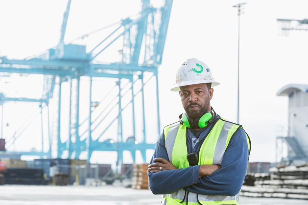 Worker in hard hat standing in front of cranes