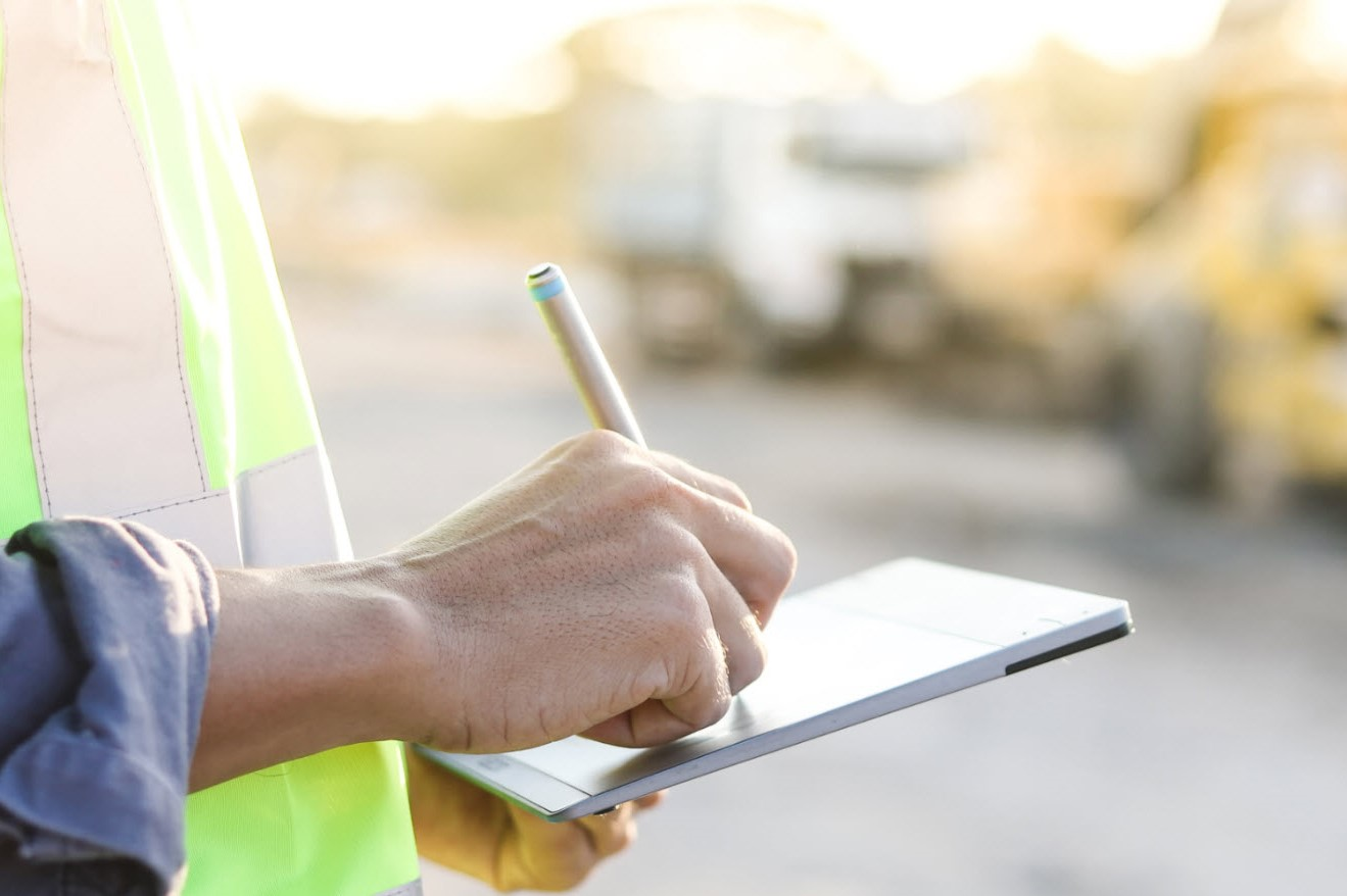Worker writing on a notepad