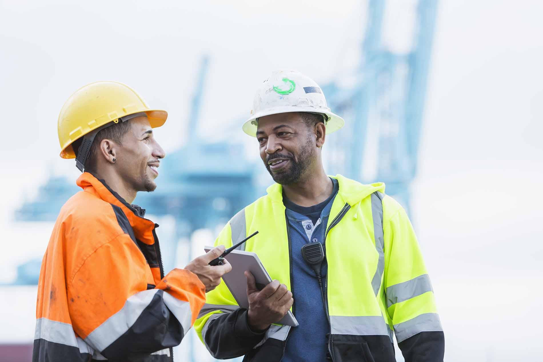 Workers in hard hats talking
