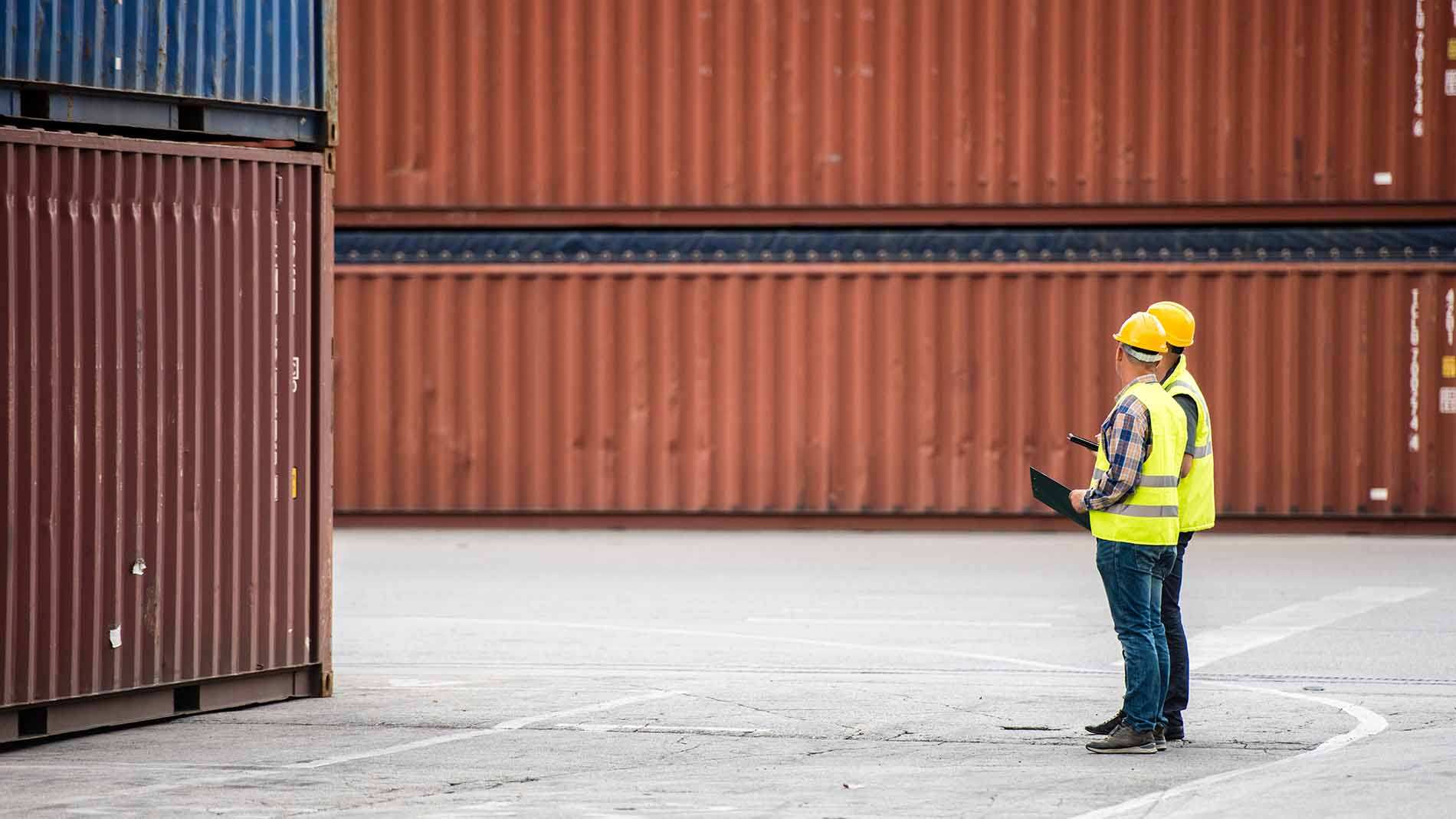 two men in front of containers